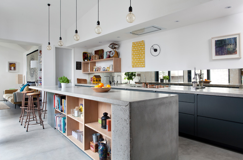 Open concept kitchen - large contemporary concrete floor and gray floor open concept kitchen idea in Other with black cabinets, concrete countertops, mirror backsplash, an island, gray countertops and flat-panel cabinets