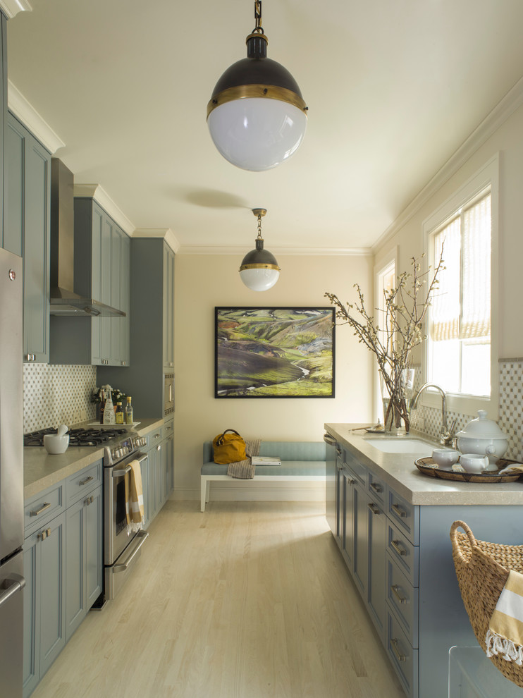 Example of a trendy galley enclosed kitchen design in San Francisco with blue cabinets, an undermount sink, recessed-panel cabinets and stainless steel appliances