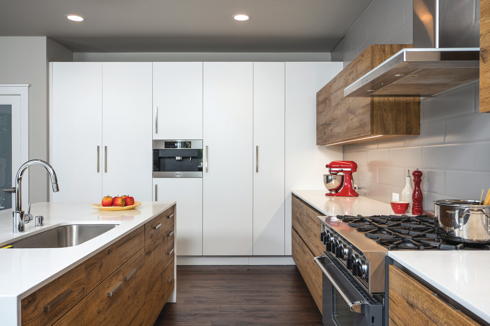 Example of a trendy galley dark wood floor kitchen design in Seattle with an undermount sink, flat-panel cabinets, medium tone wood cabinets, gray backsplash, subway tile backsplash, stainless steel appliances, an island and quartz countertops