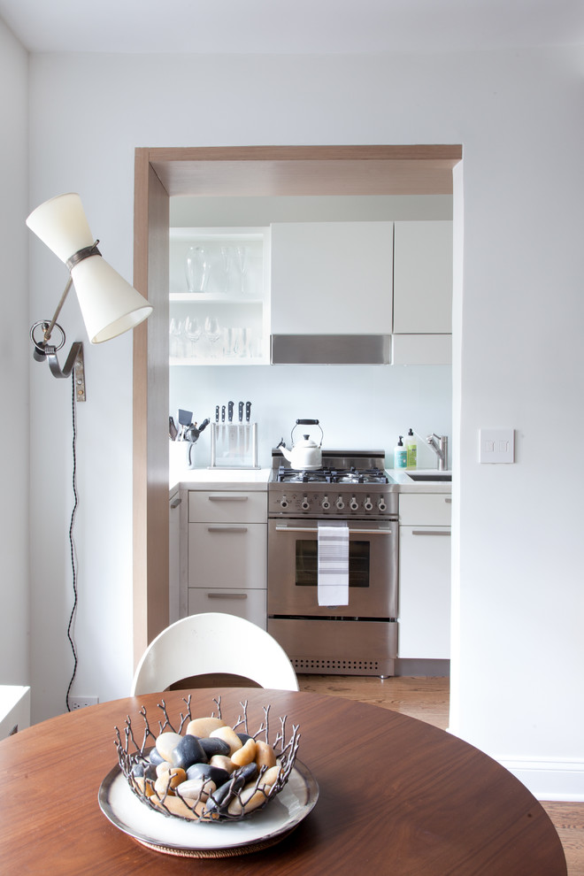 Kitchen - contemporary kitchen idea in New York with stainless steel appliances, open cabinets, white cabinets, white backsplash and glass sheet backsplash