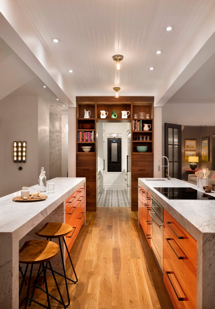 Example of a mid-sized trendy galley medium tone wood floor open concept kitchen design in Denver with two islands, an undermount sink, flat-panel cabinets, medium tone wood cabinets, marble countertops and stainless steel appliances