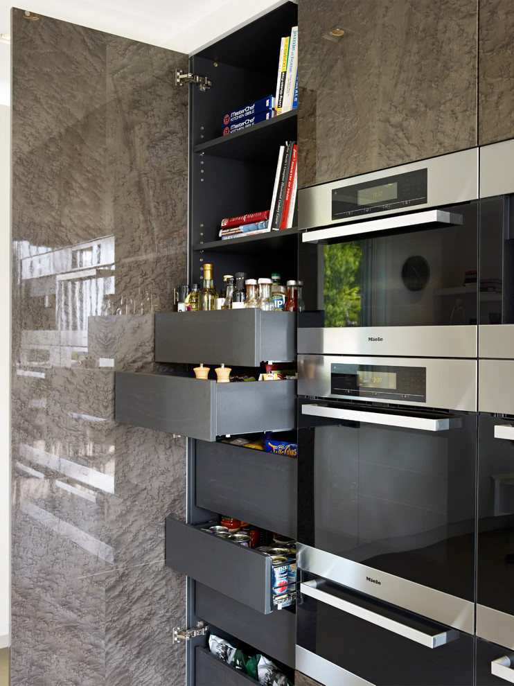 Example of a trendy kitchen design in London with flat-panel cabinets, black cabinets and stainless steel appliances