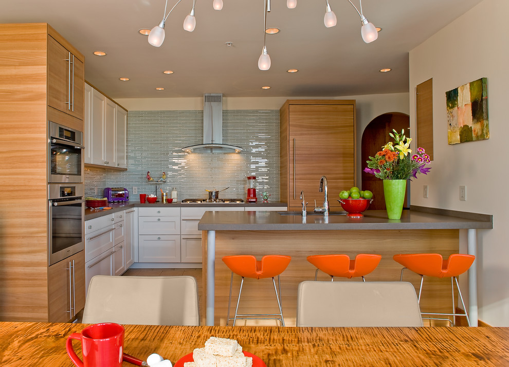 Eat-in kitchen - contemporary l-shaped eat-in kitchen idea in Boston with paneled appliances, an undermount sink, shaker cabinets, white cabinets, quartz countertops, blue backsplash and glass tile backsplash