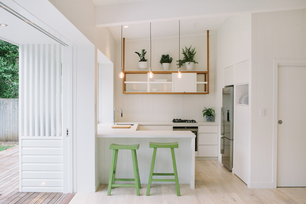 Inspiration for a small contemporary u-shaped light wood floor kitchen remodel in Other with an undermount sink, flat-panel cabinets, white cabinets and stainless steel appliances
