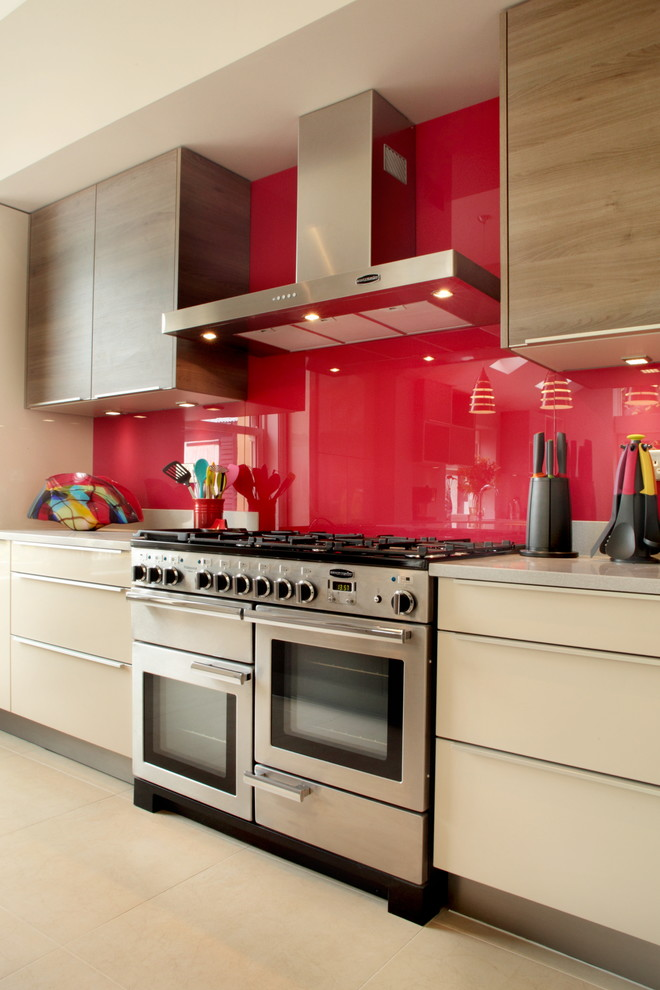 Kitchen - contemporary kitchen idea in Buckinghamshire with flat-panel cabinets, beige cabinets, red backsplash, glass sheet backsplash and stainless steel appliances