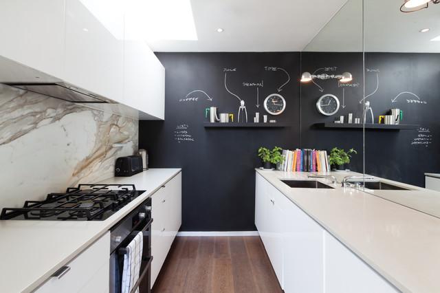 Immagine di una cucina parallela contemporanea con ante lisce, ante bianche, paraspruzzi bianco, paraspruzzi in lastra di pietra e pavimento in legno massello medio