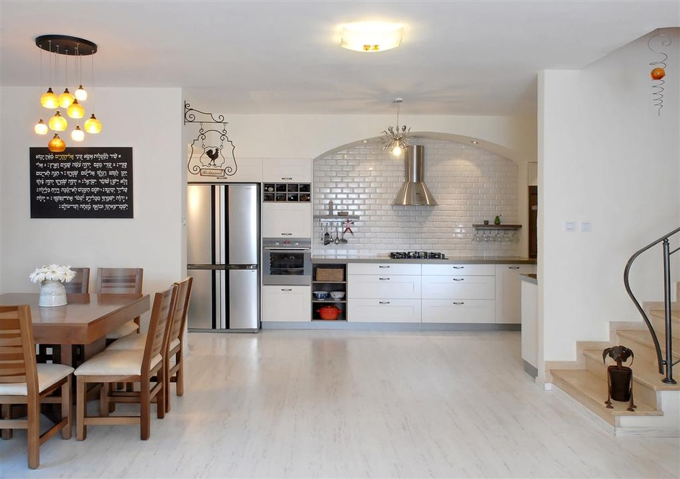 Trendy white floor kitchen photo in Other with subway tile backsplash and stainless steel appliances