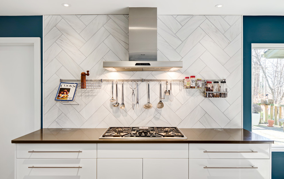 Mid-sized trendy l-shaped cork floor and beige floor enclosed kitchen photo in Other with a farmhouse sink, flat-panel cabinets, white cabinets, quartz countertops, white backsplash, stainless steel appliances, an island and stone tile backsplash