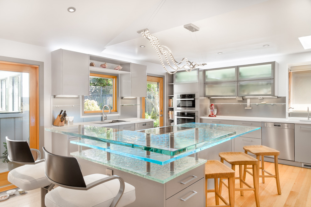 Inspiration for a large contemporary u-shaped light wood floor kitchen remodel in Los Angeles with flat-panel cabinets, glass countertops, stainless steel appliances, an undermount sink, gray cabinets, gray backsplash, an island and turquoise countertops