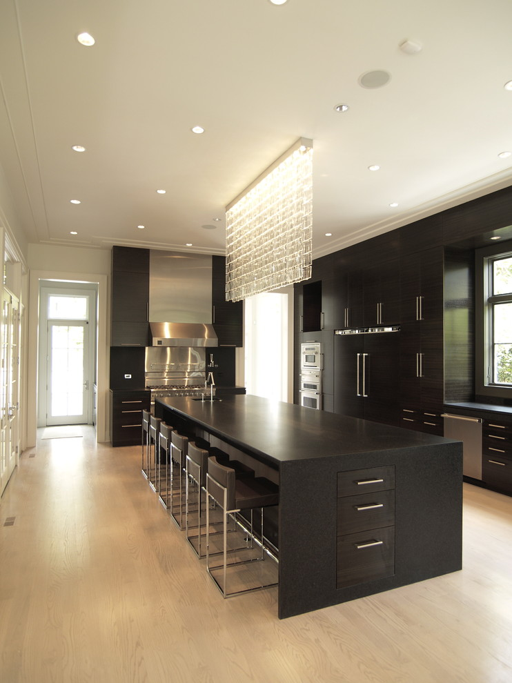 Example of a trendy kitchen design in Atlanta with paneled appliances, flat-panel cabinets, black cabinets and granite countertops
