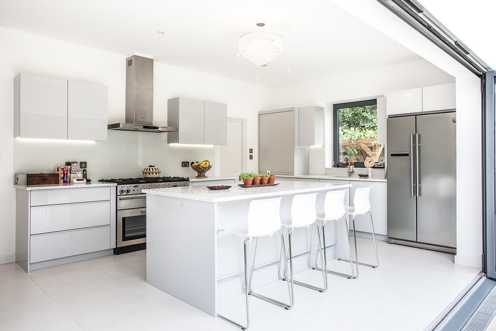 Kitchen - contemporary kitchen idea in London with a double-bowl sink, flat-panel cabinets, white cabinets, white backsplash and stainless steel appliances