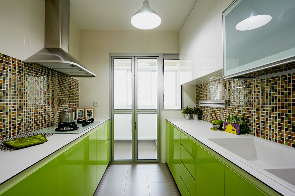 Trendy galley kitchen photo in Singapore with an integrated sink, flat-panel cabinets, green cabinets, multicolored backsplash, mosaic tile backsplash and no island