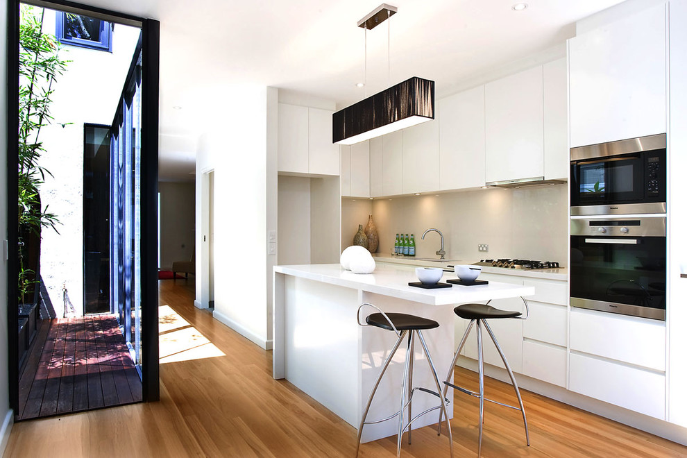 Eat-in kitchen - small contemporary galley medium tone wood floor eat-in kitchen idea in Sydney with flat-panel cabinets, white cabinets, stainless steel appliances, an undermount sink, quartz countertops, beige backsplash, glass sheet backsplash and an island