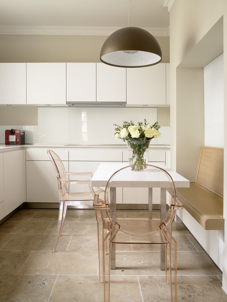 Trendy travertine floor and beige floor eat-in kitchen photo in London with flat-panel cabinets, white cabinets, white backsplash and glass sheet backsplash
