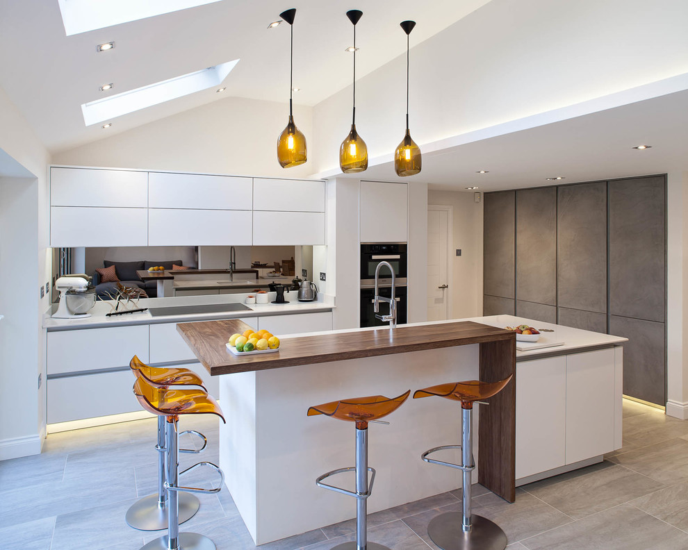 Example of a large trendy kitchen design in Hertfordshire with flat-panel cabinets, white cabinets, metallic backsplash, mirror backsplash and an island
