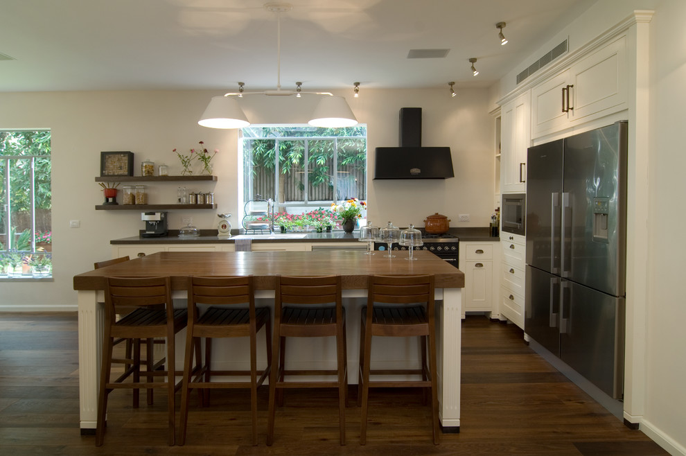 Trendy l-shaped kitchen photo in Tel Aviv with stainless steel appliances, wood countertops, recessed-panel cabinets and white cabinets