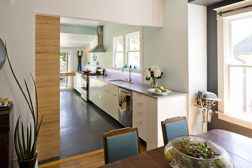 Example of a small trendy galley kitchen design in San Francisco with an undermount sink, flat-panel cabinets, white cabinets, quartz countertops, stainless steel appliances, white backsplash, ceramic backsplash and no island