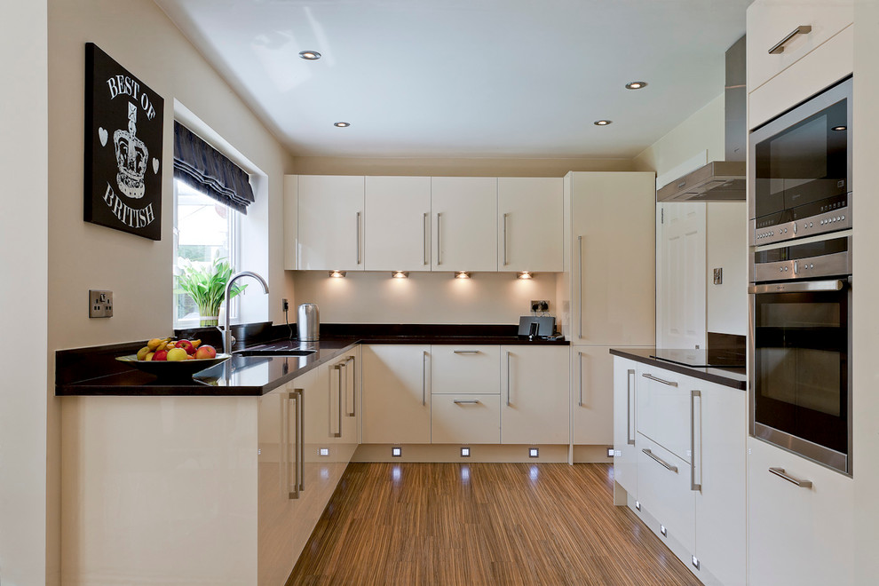 Small trendy u-shaped bamboo floor kitchen photo in Other