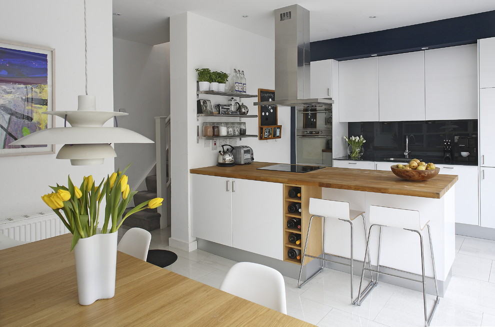 Trendy galley eat-in kitchen photo in Dublin with stainless steel appliances, wood countertops, flat-panel cabinets, white cabinets, black backsplash, glass sheet backsplash and brown countertops
