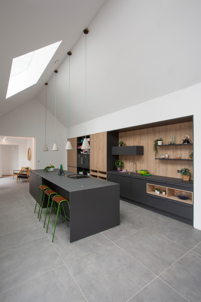 Example of a trendy l-shaped gray floor kitchen design in West Midlands with an undermount sink, flat-panel cabinets, gray cabinets, brown backsplash, wood backsplash, paneled appliances and gray countertops
