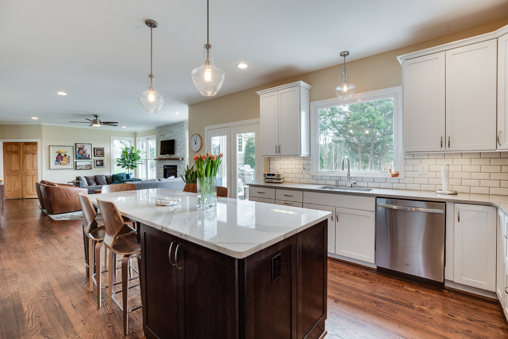 Kitchen - mid-sized contemporary u-shaped medium tone wood floor kitchen idea in DC Metro with an undermount sink, shaker cabinets, white cabinets, quartz countertops, white backsplash, stainless steel appliances and an island