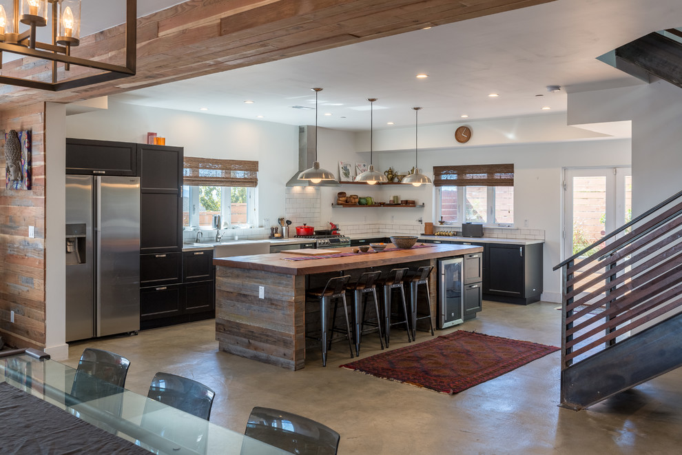 Example of a trendy l-shaped concrete floor eat-in kitchen design in San Francisco with a farmhouse sink, recessed-panel cabinets, dark wood cabinets, white backsplash, subway tile backsplash and an island