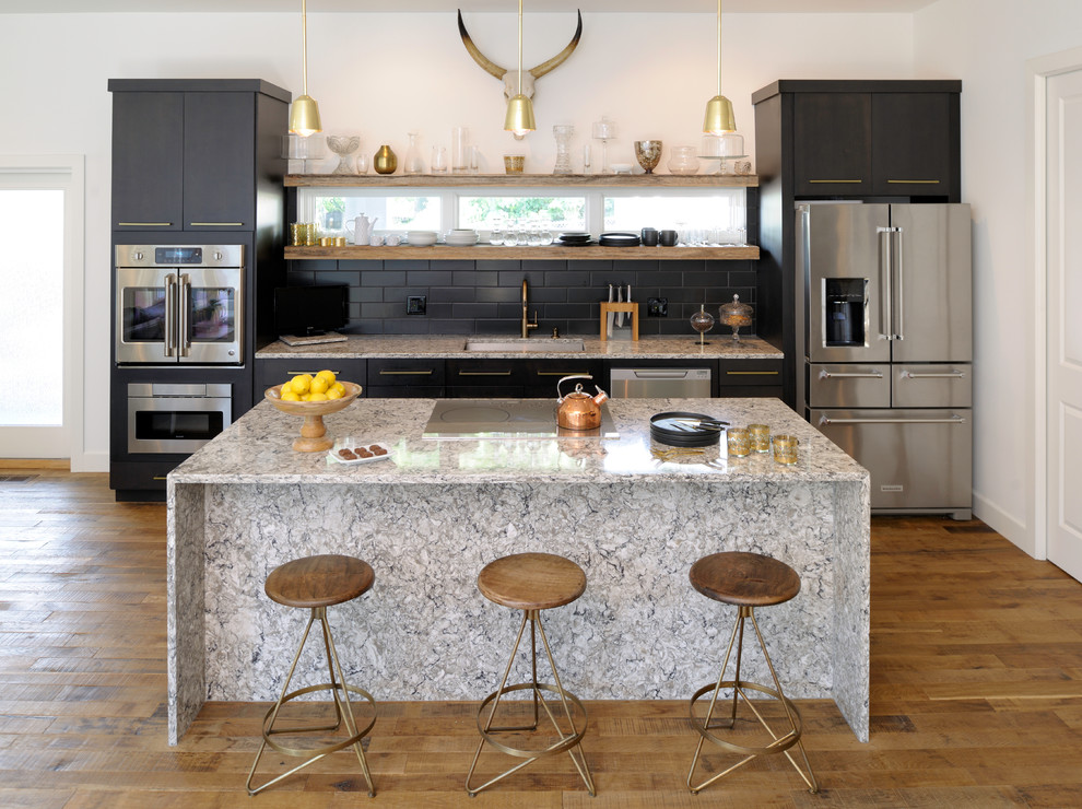 Example of a trendy single-wall medium tone wood floor open concept kitchen design in St Louis with an undermount sink, flat-panel cabinets, black cabinets, black backsplash, subway tile backsplash, stainless steel appliances, an island, granite countertops and gray countertops