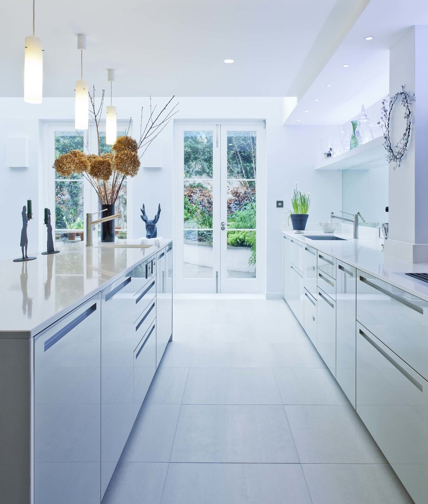 Contemporary galley kitchen in London with flat-panel cabinets and grey cabinets.