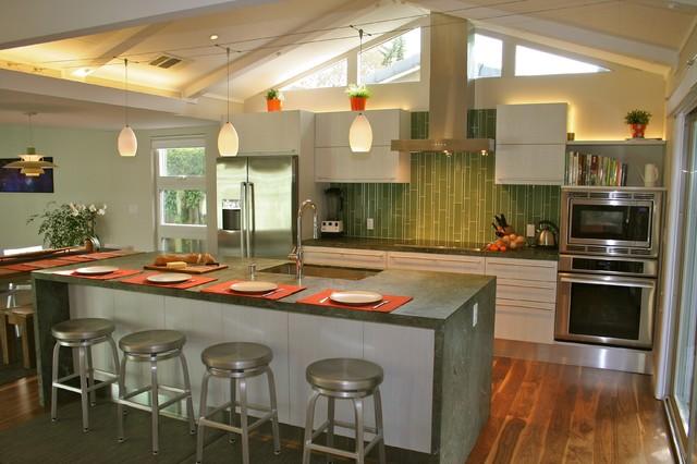 Example of a mid-sized minimalist galley medium tone wood floor open  concept kitchen design
