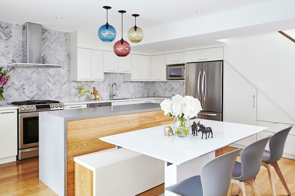 Inspiration for a contemporary medium tone wood floor kitchen remodel in Toronto with an undermount sink, flat-panel cabinets, white cabinets, gray backsplash, stainless steel appliances and an island