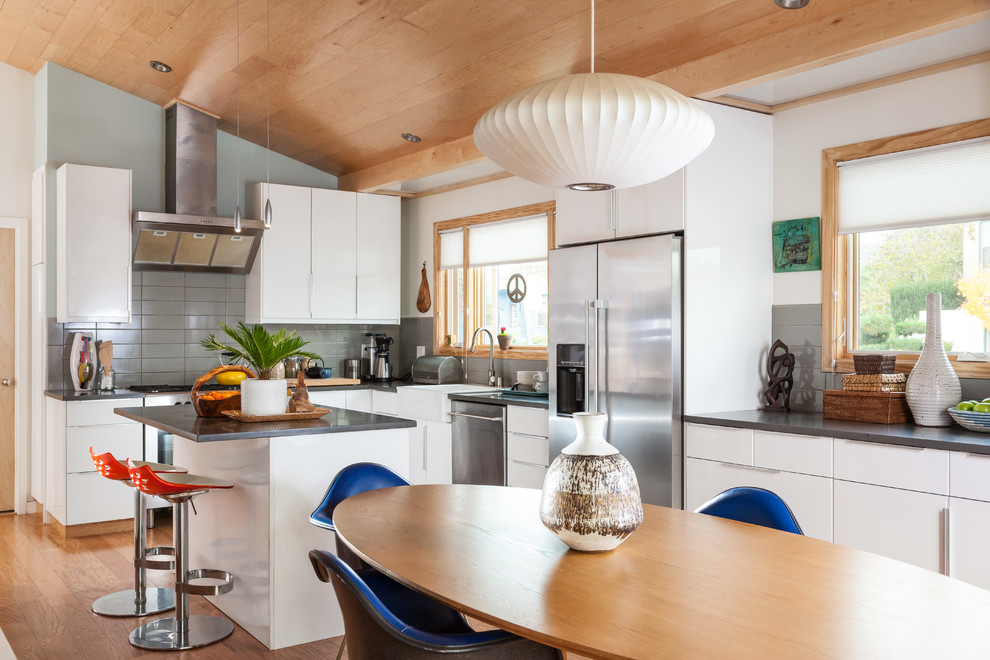 Eat-in kitchen - 1960s l-shaped medium tone wood floor eat-in kitchen idea in San Francisco with a farmhouse sink, flat-panel cabinets, white cabinets, quartz countertops, gray backsplash, ceramic backsplash, stainless steel appliances and an island