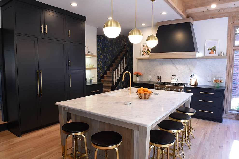 Inspiration for a large contemporary u-shaped light wood floor and beige floor kitchen remodel in Cleveland with an undermount sink, shaker cabinets, black cabinets, white backsplash, an island, quartz countertops, stone slab backsplash and paneled appliances