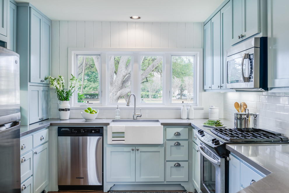 Elegant u-shaped kitchen photo in Austin with a farmhouse sink, shaker cabinets, blue cabinets, stainless steel appliances, no island, white backsplash, subway tile backsplash and solid surface countertops