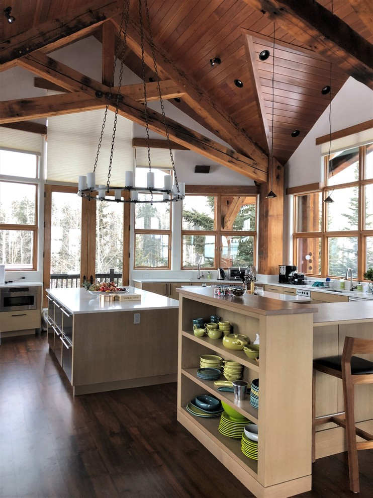 Eat-in kitchen - huge rustic u-shaped dark wood floor and brown floor eat-in kitchen idea in Denver with an undermount sink, flat-panel cabinets, light wood cabinets, stainless steel appliances, two islands and white countertops