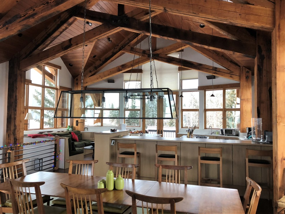 Inspiration for a huge rustic u-shaped dark wood floor and brown floor eat-in kitchen remodel in Denver with an undermount sink, flat-panel cabinets, light wood cabinets, stainless steel appliances, two islands and white countertops