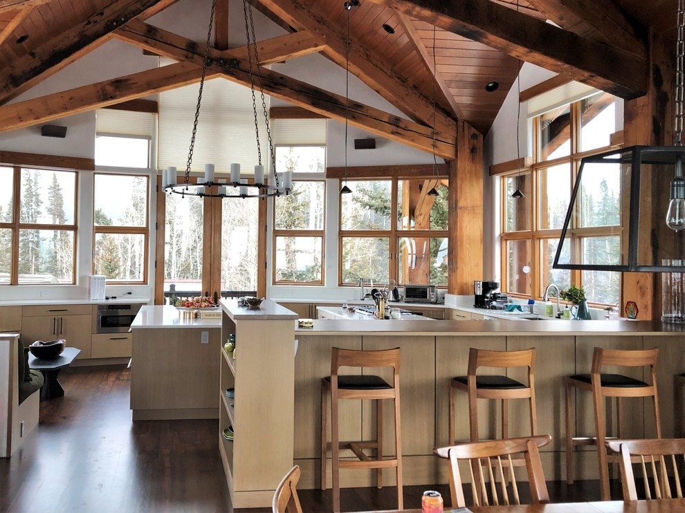 Huge mountain style u-shaped dark wood floor and brown floor eat-in kitchen photo in Denver with an undermount sink, flat-panel cabinets, light wood cabinets, stainless steel appliances, two islands and white countertops