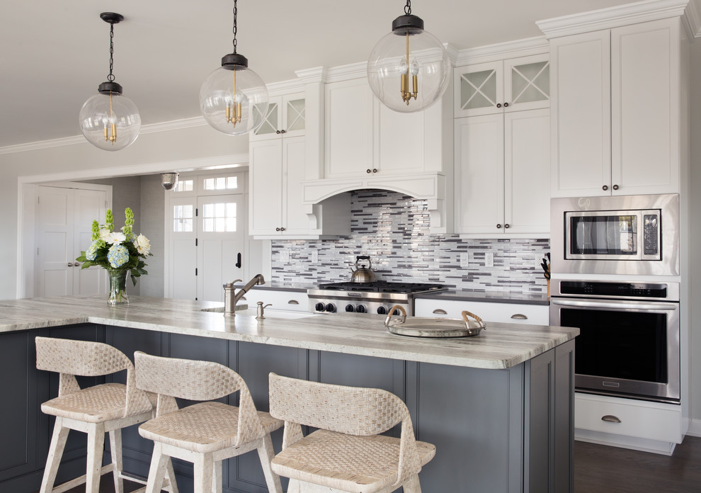Open concept kitchen - large coastal l-shaped dark wood floor and brown floor open concept kitchen idea in New York with a farmhouse sink, beaded inset cabinets, white cabinets, gray backsplash, matchstick tile backsplash, stainless steel appliances and an island