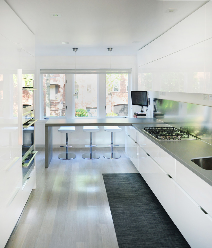 Mid-sized trendy l-shaped light wood floor kitchen photo in DC Metro with flat-panel cabinets, white cabinets, an undermount sink, quartzite countertops, metallic backsplash, metal backsplash, stainless steel appliances and a peninsula