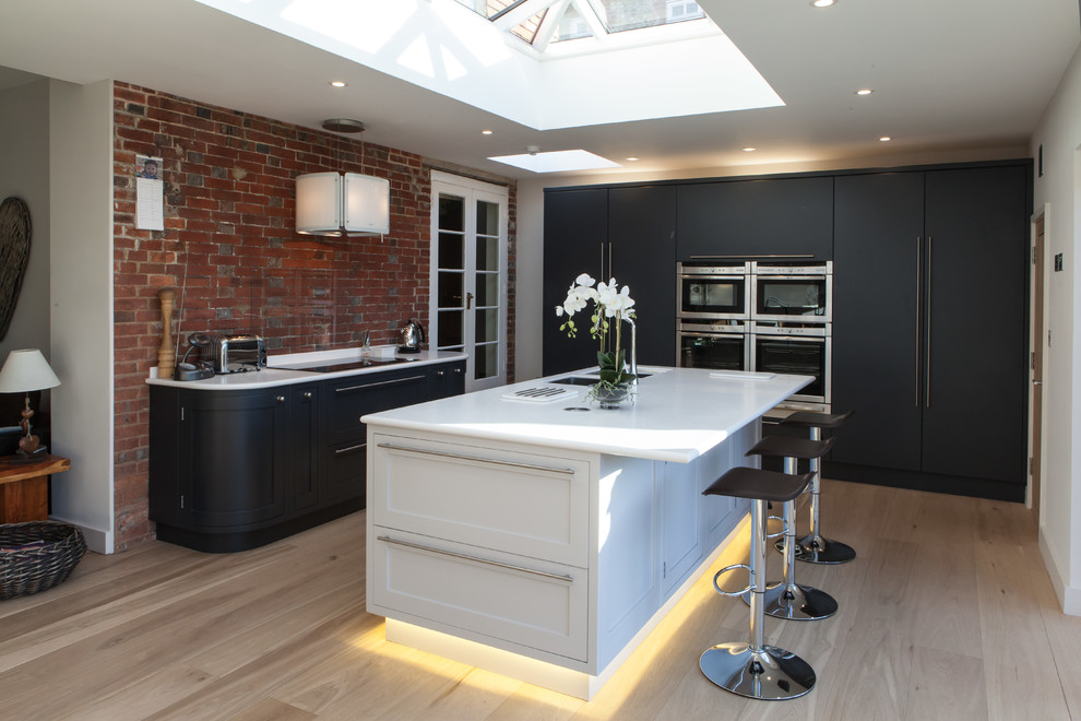 Trendy l-shaped light wood floor kitchen photo in Hampshire with a double-bowl sink, flat-panel cabinets, gray cabinets, glass sheet backsplash, paneled appliances and an island