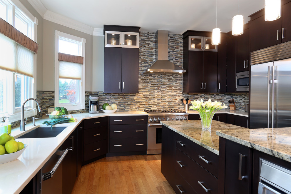 Example of a large trendy u-shaped light wood floor eat-in kitchen design in Chicago with an undermount sink, flat-panel cabinets, dark wood cabinets, granite countertops, multicolored backsplash, mosaic tile backsplash, stainless steel appliances and an island