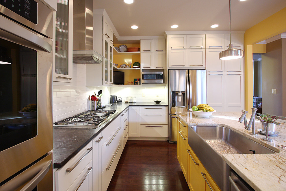 Inspiration for a transitional kitchen remodel in DC Metro with stainless steel appliances, yellow cabinets, a farmhouse sink, white backsplash and subway tile backsplash