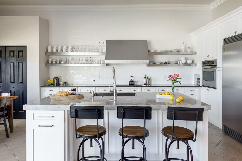 Eat-in kitchen - large traditional galley porcelain floor eat-in kitchen idea in Miami with an undermount sink, shaker cabinets, white cabinets, marble countertops, white backsplash, subway tile backsplash, stainless steel appliances and an island