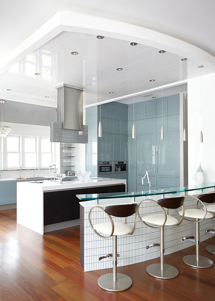 Large trendy u-shaped medium tone wood floor open concept kitchen photo in Miami with an undermount sink, flat-panel cabinets, blue cabinets, metal backsplash, stainless steel appliances and two islands
