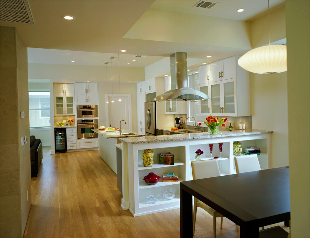 Example of a transitional l-shaped open concept kitchen design in Austin with stainless steel appliances, glass-front cabinets, white cabinets and granite countertops