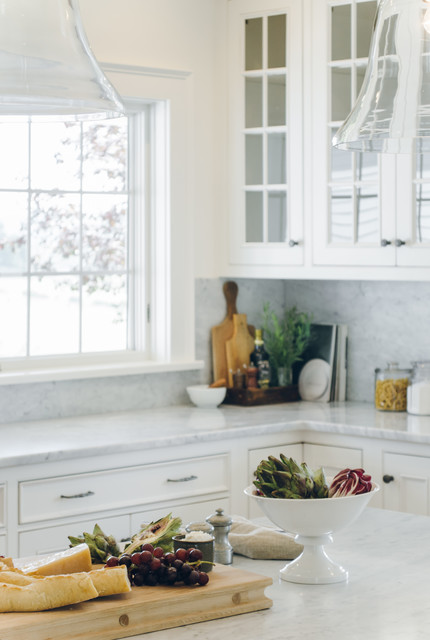Inspiration for a large country u-shaped medium tone wood floor eat-in kitchen remodel in New York with a farmhouse sink, beaded inset cabinets, white cabinets, marble countertops, white backsplash, stone slab backsplash, stainless steel appliances and an island
