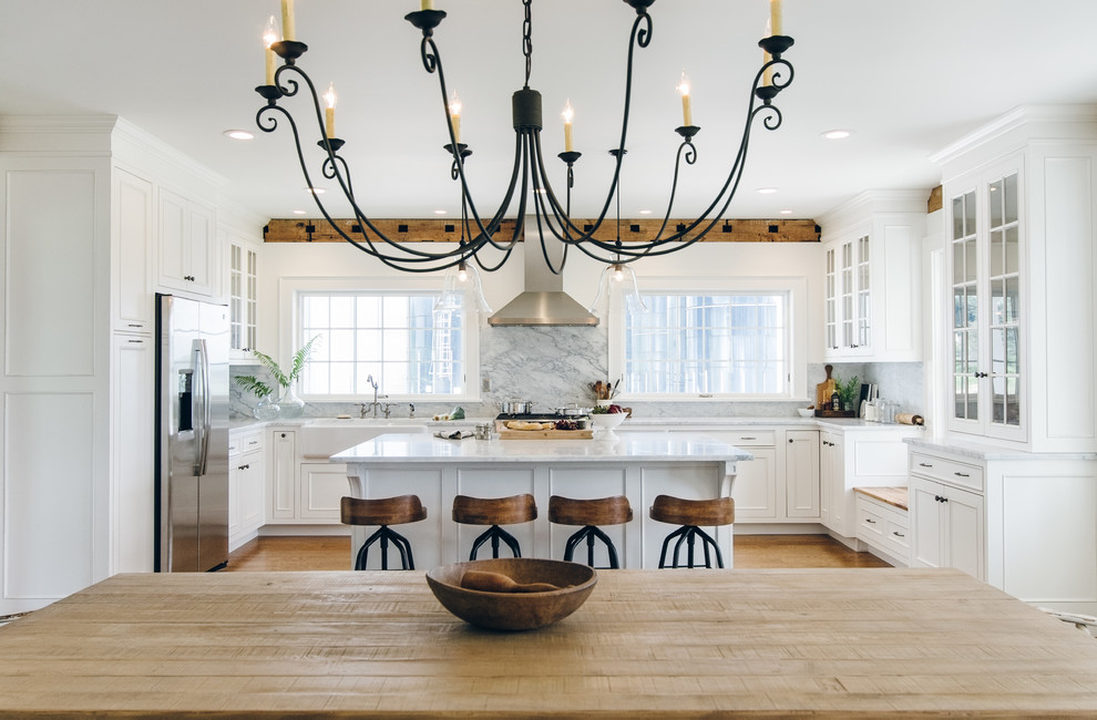 Eat-in kitchen - large cottage u-shaped medium tone wood floor eat-in kitchen idea in New York with a farmhouse sink, beaded inset cabinets, white cabinets, marble countertops, white backsplash, stone slab backsplash, stainless steel appliances and an island