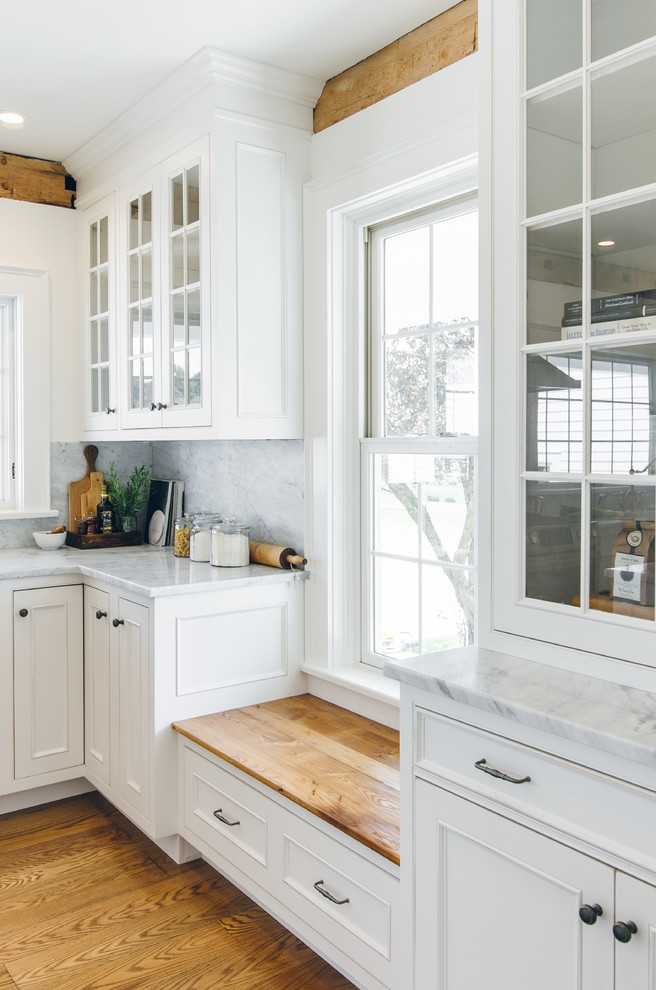 Example of a large country medium tone wood floor eat-in kitchen design in New York with a farmhouse sink, beaded inset cabinets, white cabinets, marble countertops, white backsplash, stone slab backsplash, stainless steel appliances and an island