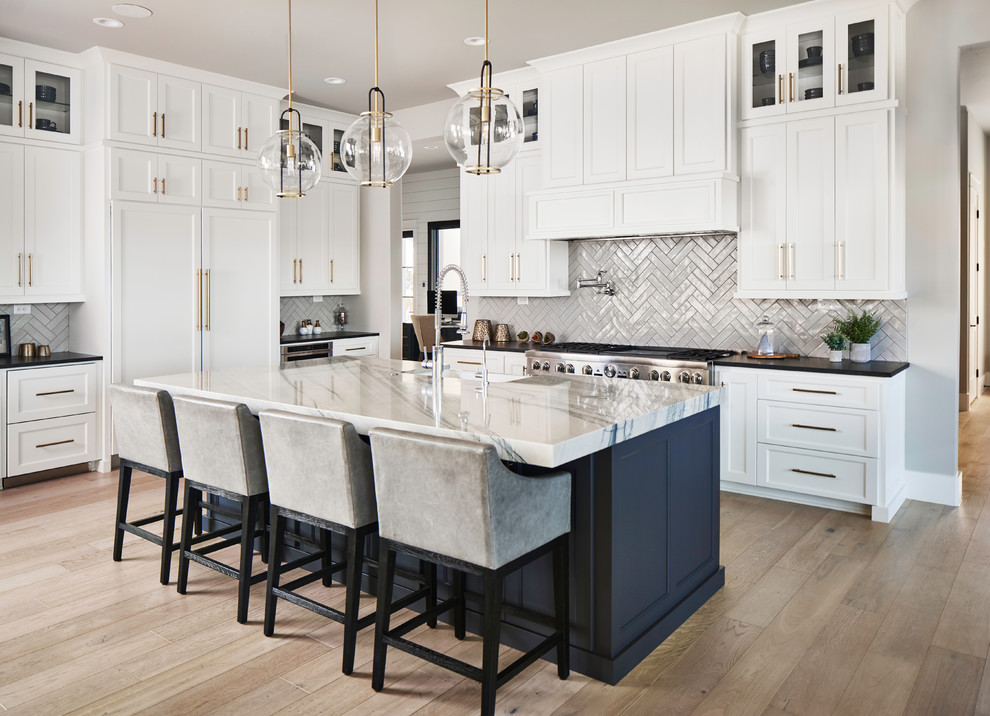 Inspiration for a transitional u-shaped medium tone wood floor and brown floor open concept kitchen remodel in Other with a farmhouse sink, shaker cabinets, white cabinets, subway tile backsplash, paneled appliances, an island and black countertops