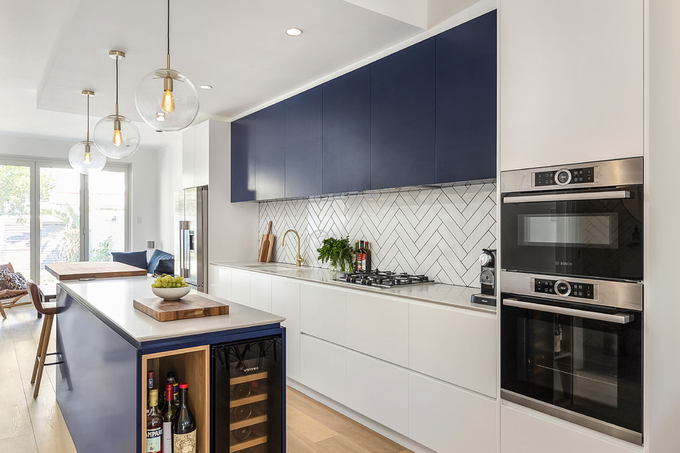 This is an example of a large contemporary galley open plan kitchen in Sydney with an undermount sink, flat-panel cabinets, blue cabinets, white splashback, subway tile splashback, light hardwood floors, an island, white benchtop, quartz benchtops, stainless steel appliances and brown floor.