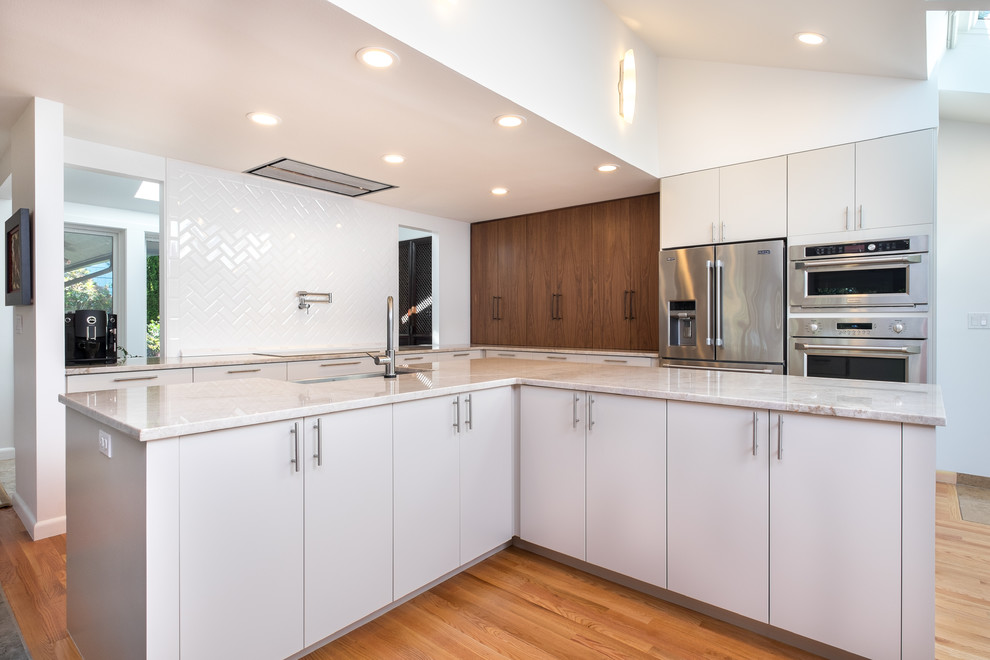 Inspiration for a large transitional l-shaped medium tone wood floor open concept kitchen remodel in Portland with an undermount sink, flat-panel cabinets, white cabinets, quartzite countertops, white backsplash, ceramic backsplash, stainless steel appliances and an island
